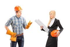 有男性的体力工人与女性建筑师的一次交谈 免版税库存图片