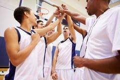 有男性高中的蓝球队与教练的队谈话 免版税图库摄影