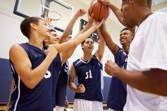 有男性高中的蓝球队与教练的队谈话