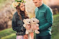 有男朋友和两长毛绒玩具熊的愉快的女孩 免版税库存图片