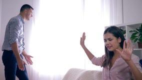 有男朋友尖叫的恼怒的女孩在彼此在争吵和愤怒的挥动的手期间在屋子里 股票视频