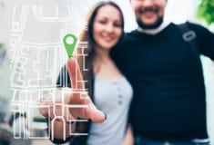 有男朋友的妇女旅客指向在地图的一个手指 看法通过电话屏幕 库存照片