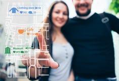 有男朋友的妇女旅客指向在地图的一个手指 看法通过电话屏幕 免版税图库摄影