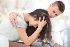 有男朋友的年轻沮丧的妇女在家坐沙发 库存照片