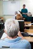 有男老师的学生计算机类的 免版税库存照片