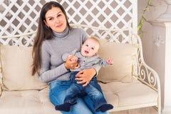 有男婴的愉快的母亲在屋子里 免版税库存图片