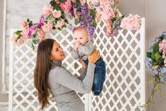 有男婴的愉快的母亲在屋子里 免版税库存照片