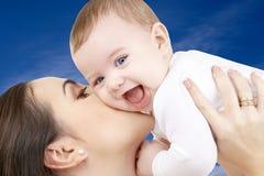 有男婴的愉快的母亲在蓝天 库存图片