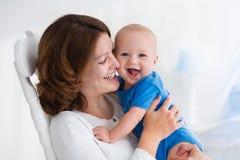 有男婴的愉快的年轻母亲在家 库存照片