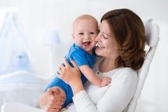有男婴的愉快的年轻母亲在家 库存图片