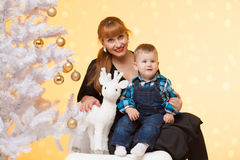 有男婴的美丽的长的头发妇女和鹿在圣诞树附近戏弄 图库摄影