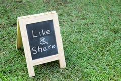 有画架的黑板和字词在绿草喜欢并且分享 免版税库存照片
