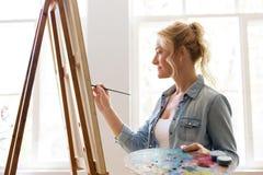 有画架绘画的妇女艺术家在艺术演播室 免版税库存照片