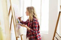 有画架绘画的学生女孩在艺术学校 免版税库存照片