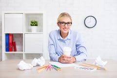 有画笔、五颜六色的铅笔和咖啡的女性设计师考虑新的想法的在办公室 免版税库存图片