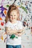 有画笔的微笑的小女孩在杂乱背景 免版税图库摄影