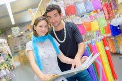 有画象愉快的夫妇乐趣尝试的服装 免版税图库摄影