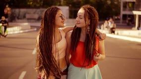 有畏惧的两名愉快的妇女走在空的路和谈在夏天 两个行家女孩笑,拥抱和 股票视频