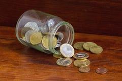 有疏散的欧洲硬币的玻璃瓶子 免版税图库摄影