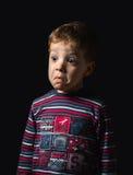 有疑义面孔的迷茫的男孩在黑背景 免版税库存照片