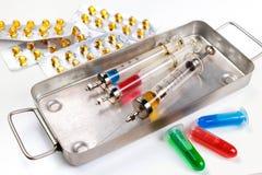 有疗程的注射器在绝育箱子、天线罩包装和小瓶有流体的白色表面上 免版税图库摄影