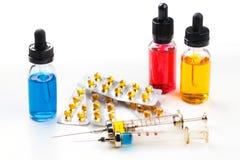 有疗程的注射器,与药片的有色的流体的天线罩包装和瓶在白色背景 免版税库存照片