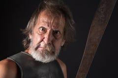 有疯狂的神色的恼怒的老有胡子的战士 免版税库存图片