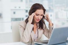 有疲乏的女实业家头疼,当工作在她的lapto时 免版税库存照片