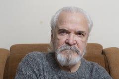 有疼痛眼睛的孤独的老人 免版税库存照片