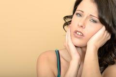有痛苦的牙痛的可爱的不快乐的被注重的少妇 免版税库存图片