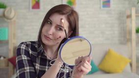 有痣的年轻沮丧的妇女在她的看在镜子和做构成关闭的面孔  股票视频