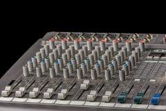 有瘤的音频混合的控制台和滑子和黑背景 免版税库存照片