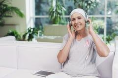 有癌症的一名妇女坐在一个现代诊所的一个白色沙发 她有在她的衬衣的一条桃红色丝带 免版税库存照片