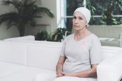 有癌症的一名妇女坐在一个现代诊所的一个白色沙发 她有在她的衬衣的一条桃红色丝带 免版税图库摄影