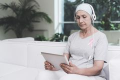 有癌症的一名妇女坐在一个现代诊所的一个白色沙发 她有在她的衬衣的一条桃红色丝带 库存照片