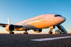有登机梯的白色大型客机在平衡的太阳的机场围裙 免版税库存图片