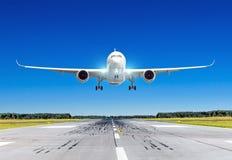 有登陆在与蓝天的好晴天的明亮的着陆指示灯的乘客飞机在跑道 免版税库存图片