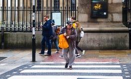 有白发和sweatpants的年迈的人在Lo穿过在大英博物馆前面的路与购物袋-看左为交通 免版税库存照片