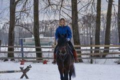 有白发的一个女孩学会骑马 女孩最近开始实践马术 女孩害怕ri 图库摄影