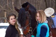 有白发的两个女孩与他们的马沟通 女孩完成的骑马马 一个多云冬日 特写镜头 免版税库存照片