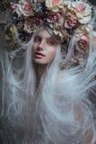 有白发的妇女和白玫瑰和雪 免版税库存照片