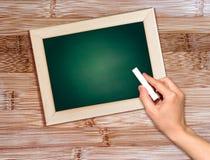 有白垩文字的手在黑板。 免版税库存照片
