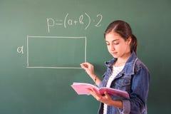 有白垩的女小学生在黑板解决一数学问题 免版税图库摄影