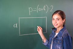 有白垩的女小学生在黑板解决一数学问题 免版税库存图片