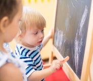 有白垩的小孩在黑板侧视图附近 免版税图库摄影