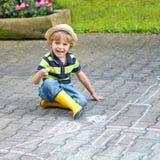 绘有白垩的小男孩一辆拖拉机车在夏天 免版税库存照片