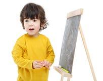 有白垩的小男孩站立近的黑板 免版税库存图片