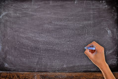 有白垩的手,开始写在空白的背景 库存照片