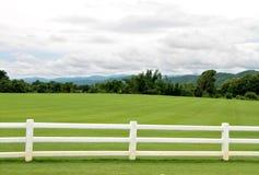 有白水泥篱芭和多云天空的绿色牧场地 免版税库存照片