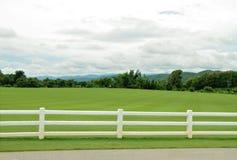 有白水泥篱芭和多云天空的绿色牧场地 图库摄影